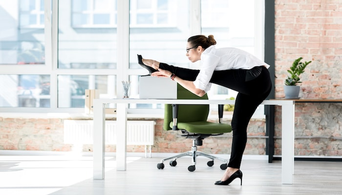 Woman ding desk exercises   DNAfit Blog