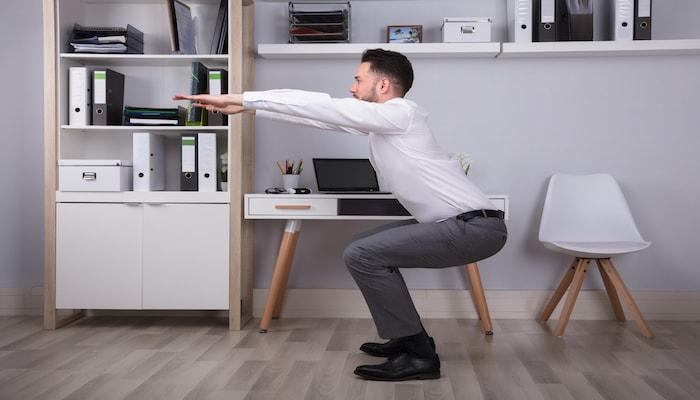 Man doing squats at the office   DNAfit Blog
