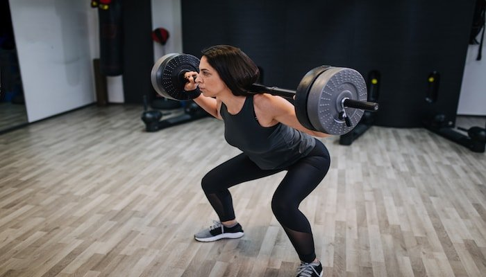 Woman doing weighted squats at the gym | DNAfit Blog