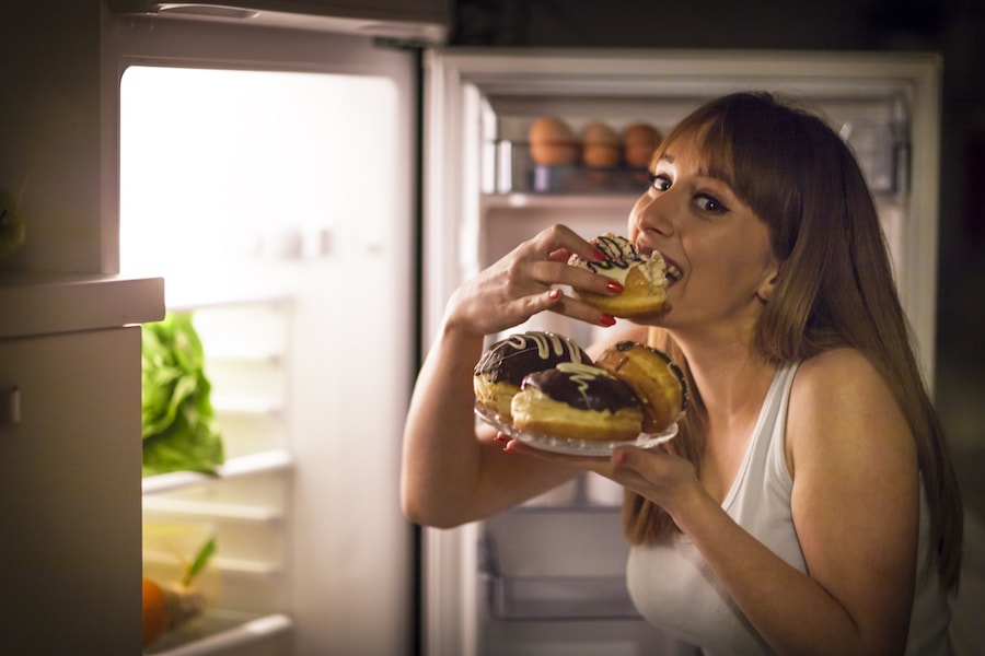 Women eating donuts from fridge | DNAfit Blog