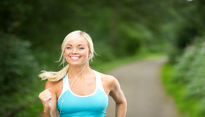 Lady jogging and listening to music | DNAfit Blog