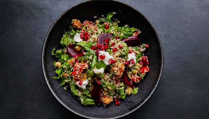 Salad lunch bowl of greens beetroot sesame seeds tomato and feta cheese with pomegranate