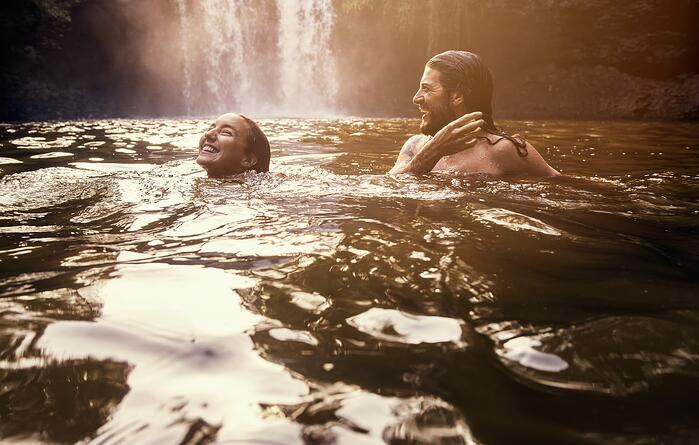 A man and woman smiling and swimming in a river by a waterfall.